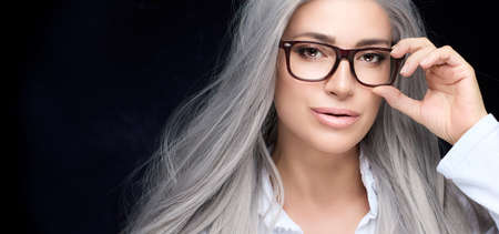 Beautiful gray-haired mature woman wearing fashionable glasses holding her hand to the frames as she looks quietly at the camera with parted lips in a cropped panorama view with copyspace on black