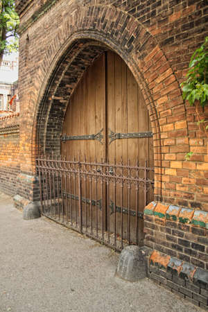 ironwork: Hospital Apolinar , doors decorated with ironwork. Before the gate grid  wooden doors , decorative made into an arc , studded with spikes. Old Prague. nice example of old craftsmen work with brick and wood.
