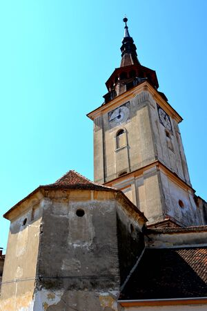 severely: Fortified medieval church in the village Sanpetru, Transylvania.  The landmark of the village is the 13th-century fortified church. The Order of Cistercians received it in 1240. The fortified church was severely destroyed during a Turkish invasion in 1432 Stock Photo
