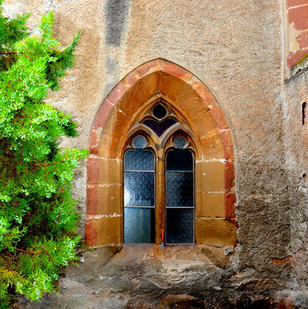 CWindow in the fortified medieval church Ghimbav, Transylvania The town was first mentioned in a letter written in 1420 by King Sigismund of Luxembourg. The local church and the bell tower were built around 1300. In the 15th century a fortress was built a Stock Photo