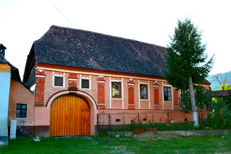 main entrance: Typical house in the village Saschiz. Medieval fortified saxon church Saschiz Keisd, Transylvania. The fortified church is a church in Keisd Wurmloch in the Transylvania region of Romania. It was built by the ethnic German Transylvanian Saxon community. T Stock Photo