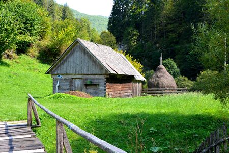 Typical house. Landscape in Apuseni Mountains, Transylvania The Apuseni Mountains is a mountain range in Transylvania, Romania, which belongs to the Western Romanian Carpathians, also called Occidentali in Romanian. The Apuseni Mountains have about 400 ca Stock Photo