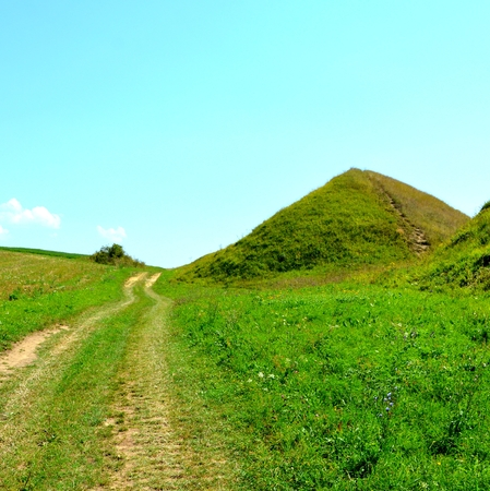 Celtic tombs. Typical rural landscape in the plains of Transylvania, Romania. Green landscape in the midsummer, in a sunny day