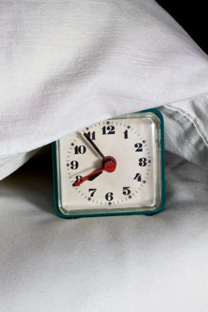 Alarm clock under pillow on the bed Stock Photo - 16729019