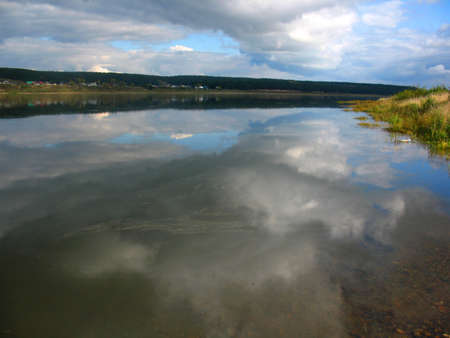 reverberation: There are  river, cloudy sky and grass on bank