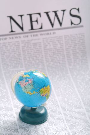 actuality: global news concept. small globe on a newspaper page.