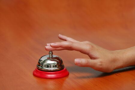 handbell: bright hand-bell on a table, hand press button Stock Photo