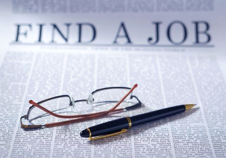 finding a job on a newspaper. searching interview information.  note: find a Job is not real newspaper headline.  photo