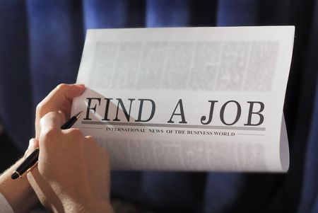 finding a job on a newspaper. searching   note:  photo