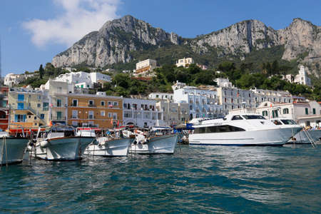 view of boat harbor or Marina Grande, on the Island of Capri, with colorful buildings , a major tourist destination near Naples and Sorrento on the Tyrrhenian Sea, Bay (Gulf) of Naples.