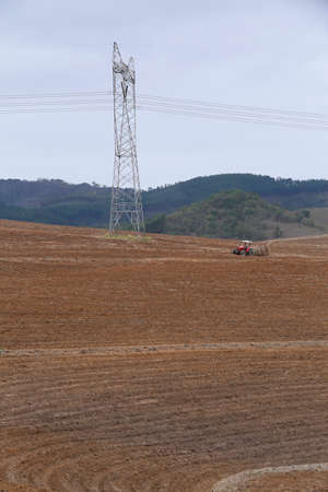 arable: Tractor ploughing rural agricultural arable fields in brazilian countryside