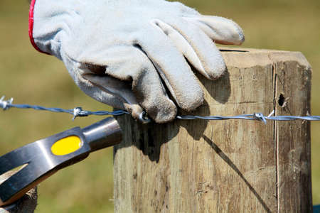 fence wire: detail of construction of new steel fence in farm on countryside in brazil