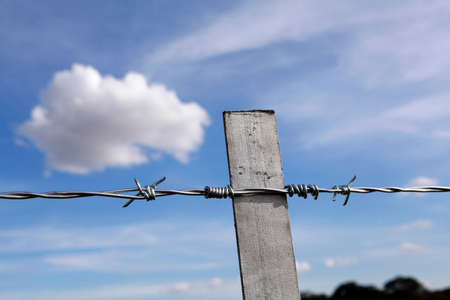 wire fence: new steel fence in farm with blue sky and clouds in background on countryside in brazil Stock Photo
