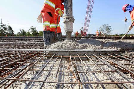 cemento: Trabajadores que vierten el cemento en la construcción de carreteras en Brasil Foto de archivo