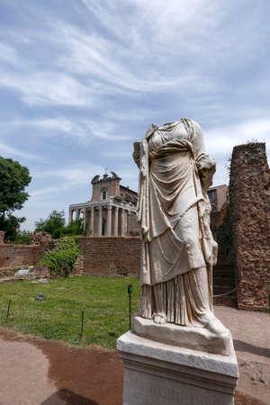 escultura romana: sculpture of vestal, forum roman, in background temple of antoninus and faustina, rome, italy