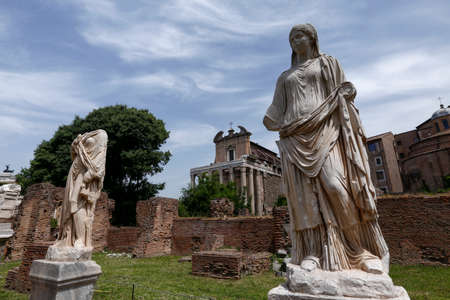 vestal: sculpture of vestal, forum roman, in background temple of antoninus and faustina, rome, italy