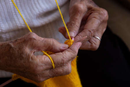Old senior woman hands wrinkled skin.Senior woman`s hand . Hands of an old woman knitting needles