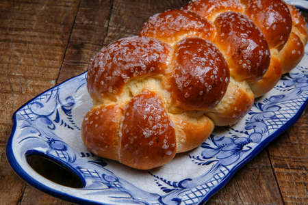 Sweet twist bread, typical of Brazilian bakery, on dish decorated in blue in rustic wooden table