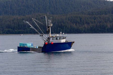 Commercial fishing boat - trawler in Pacific ocean with moutains in background. Juneau ,Alaska