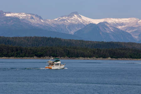 Whale watching boat searching for humpback whales in Auke Bay with snow mountain on background, Alaska