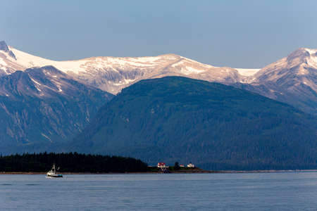 fishing boat in Auke Bay with snow mountain on background, Alaska Stock Photo