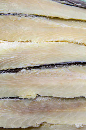 Pile of dried and salted codfish fillets on sale at a market stall.