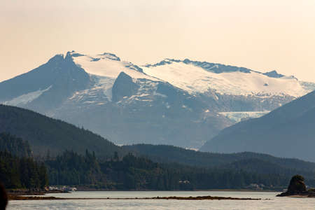 view of mountains in the snow, ocean and pine forest near Juneau, Alaska, USA