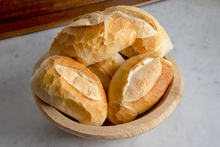 French bread style, traditional Brazilian bread on wood basket in granite table