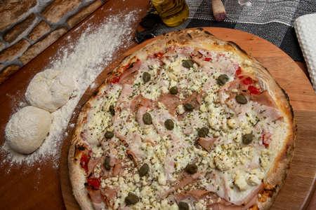 Pizza with mozzarella, rucula and dried tomato