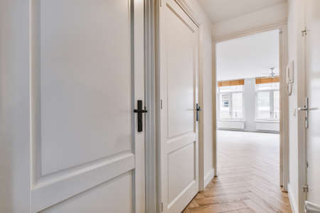 Narrow corridor with white walls and doors leading to spacious room with windows and parquet floor in modern apartment