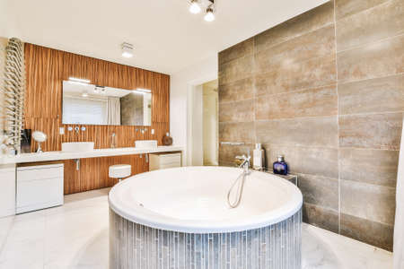 Big round shaped bathtub in big washroom with tiled walls and double sinks under mirror
