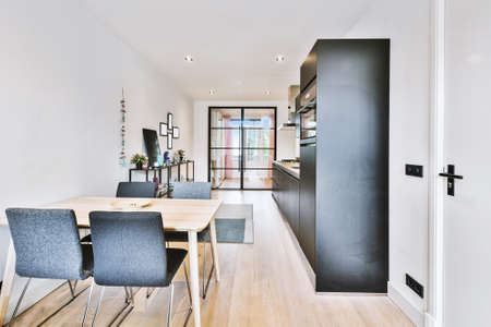 Wooden table and comfortable chairs placed near kitchen furniture in modern light flat