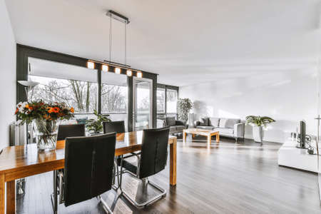 Table with chairs and flowers located under lamp against balcony entrance and lounge area in spacious room of modern apartment Banco de Imagens