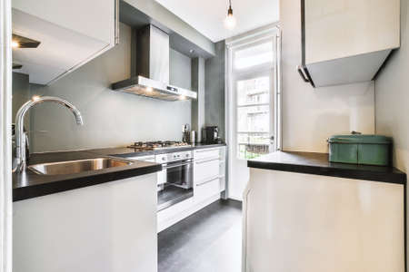 Kitchen with modern furniture and appliances near balcony door at daytime in light apartment Imagens