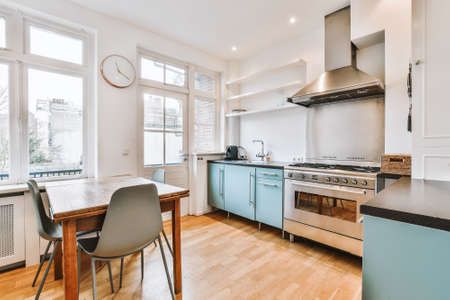 Cupboards and gas stove with exhaust hood located near table with chairs against windows in light kitchen at home
