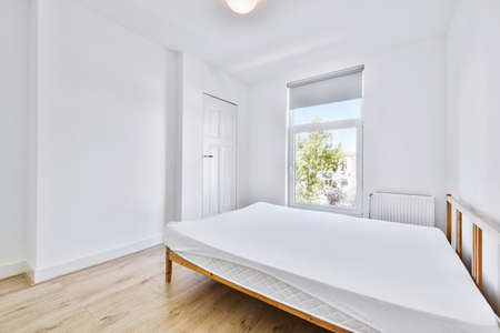 Soft mattress with white bedsheet placed on wooden bed near window in light bedroom at home Imagens