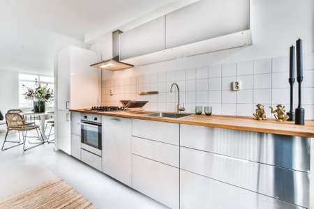 Modern home open plan kitchen with white tiles and cabinets and wooden counter equipped with stove and hood in contemporary apartment