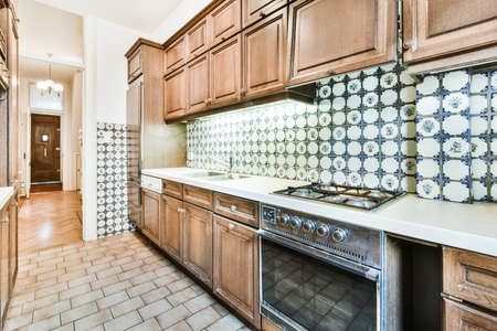 Interior design of narrow home kitchen with ceramic tile walls and floor furnished with wooden cupboards and gas stove Archivio Fotografico