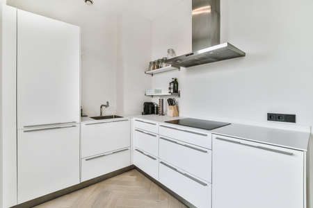 Well organized small home kitchen interior with sink and light furniture with stove in urban apartment Standard-Bild