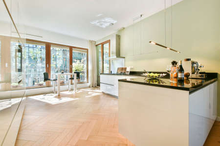 Big panoramic windows in light kitchen with white cabinets and black counter under shiny lamps Banco de Imagens