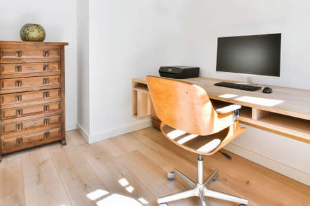 Modern interior of light study room with wooden wall mounted table and computer under shelves with books Archivio Fotografico