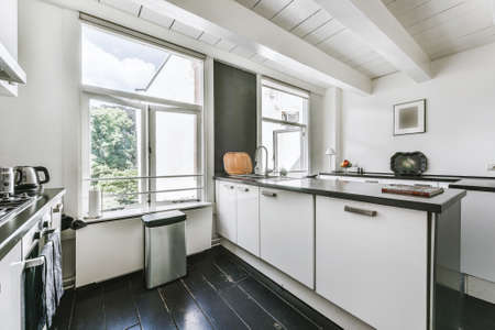 Modern furnished kitchen with black flooring and white cabinets in house with white beamed ceilings and big windows