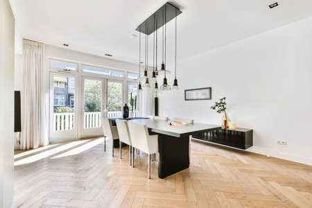 Stylish interior with parquet floor and contemporary minimalist furniture of dining table and chairs under pendant lamps