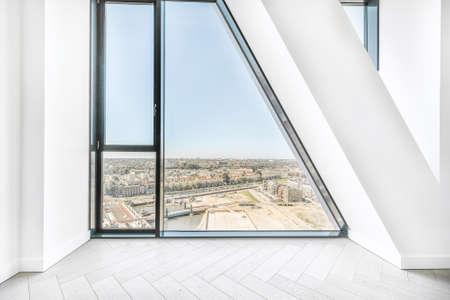 Black framed panoramic window in wall of modern apartment viewing city in bright sunlight