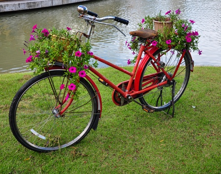 Red painted bicycle with a bucket of colorful flowers  Archivio Fotografico