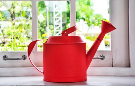 Red watering can placed in the window  photo