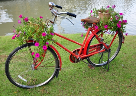 Red painted bicycle with a bucket of colorful flowers Stock Photo