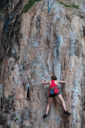 Woman climbing on the rock route summer  Railay Beach, Krabi province Thailand