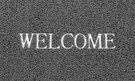 Welcome title on the gray plastic doormat for texture background. photo
