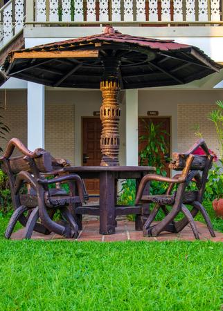 garden furniture chairs and table under wooden umbrella at garden photo